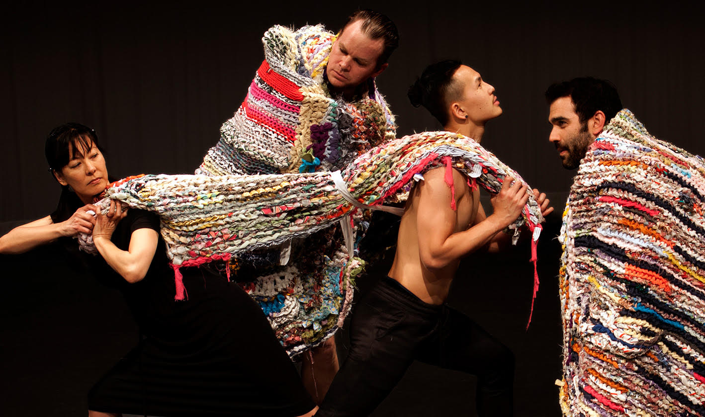 four dancers holding a crochet sculptural blanket and facing in opposing directions