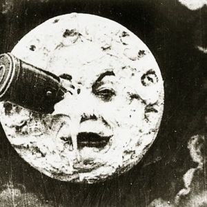Movie still from A Trip to the Moon, showing moon face with a telescope smashed into one eye
