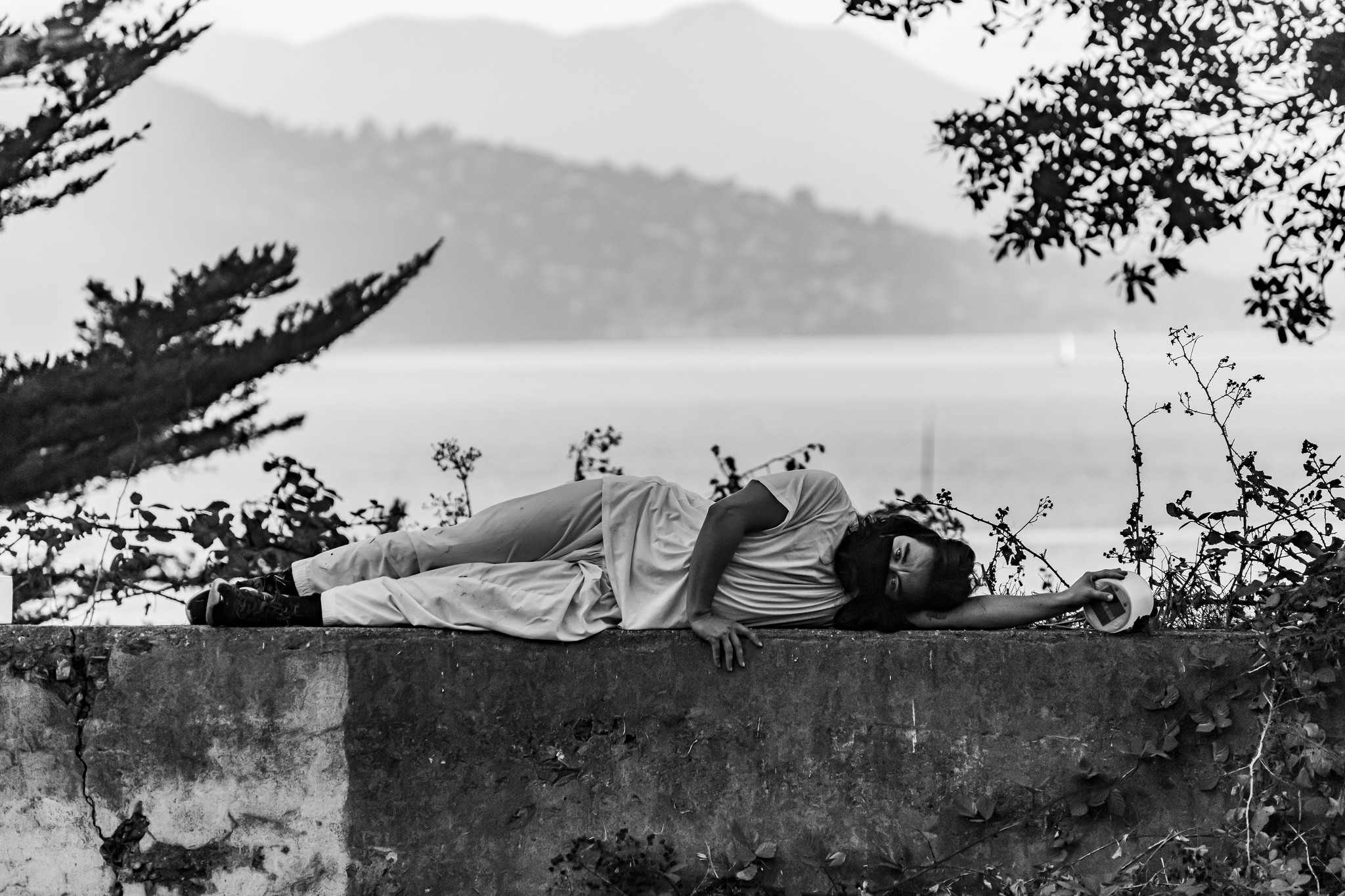 A black and white image of Daria, a mixed race person with long dark hair pulled back, wearing all white, laying on his left side on a cement ledge outside facing the camera. His left arm reaches above his head and holds a solar lantern. His right arm is crossed in front of his body, resting on the ledge in front of his belly button.